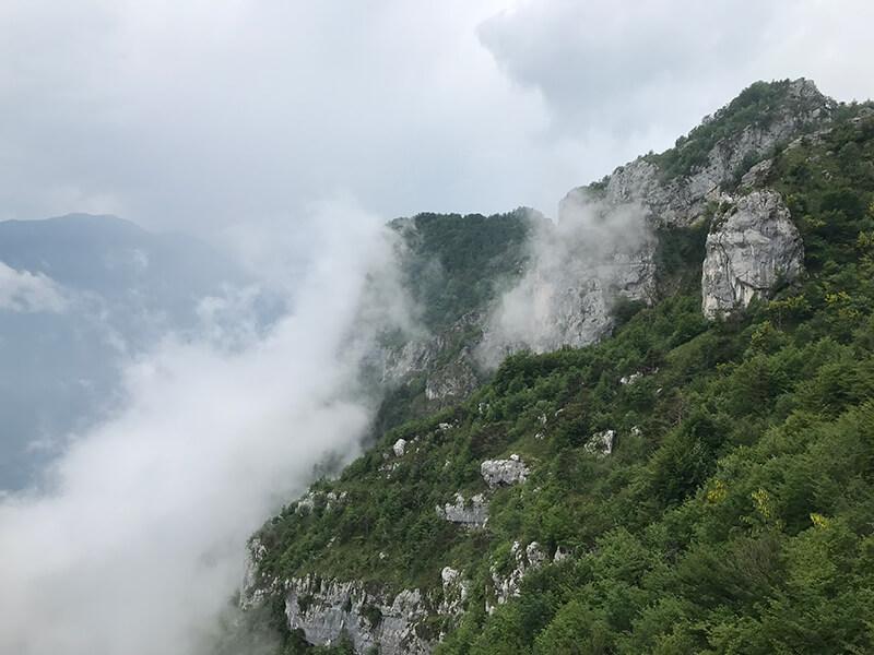 Felswände, Wolken und grüne Wälder