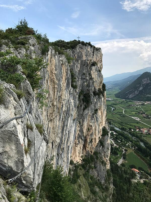 steile Felswand des Monte Colt mit Gipfelkreuz
