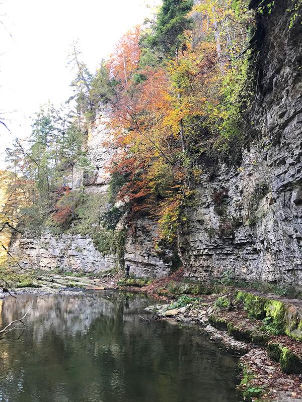 Felswände und Herbstlaub spiegeln sich im Wasser