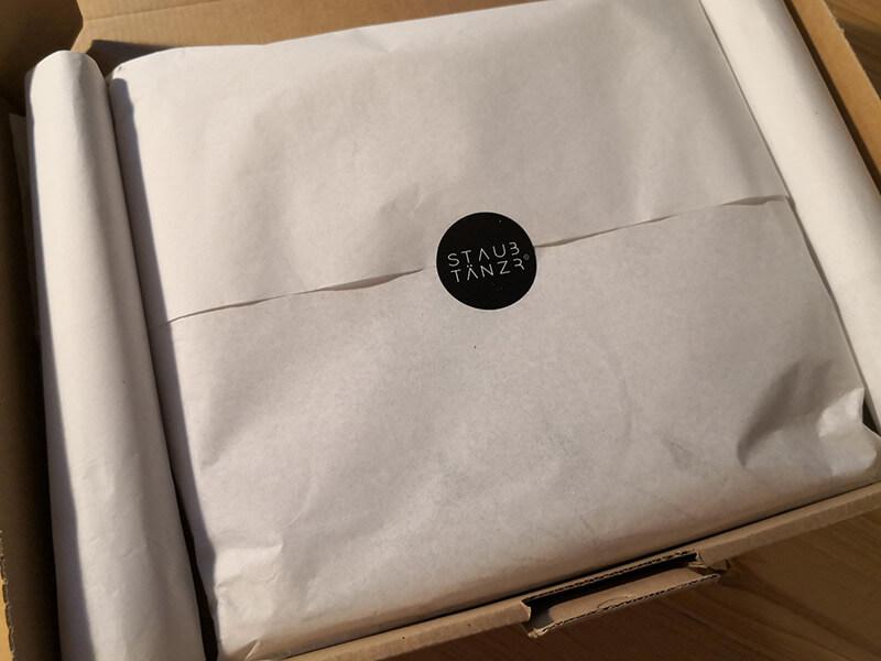 Das Shirt eingepackt in Papier mit Staubtänzer Aufkleber