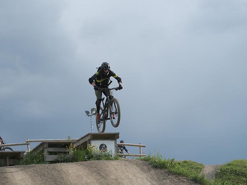 Mountainbiker beim Sprung im Übungsparcours