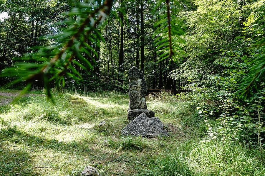 steinerner Wegweiser im Wald